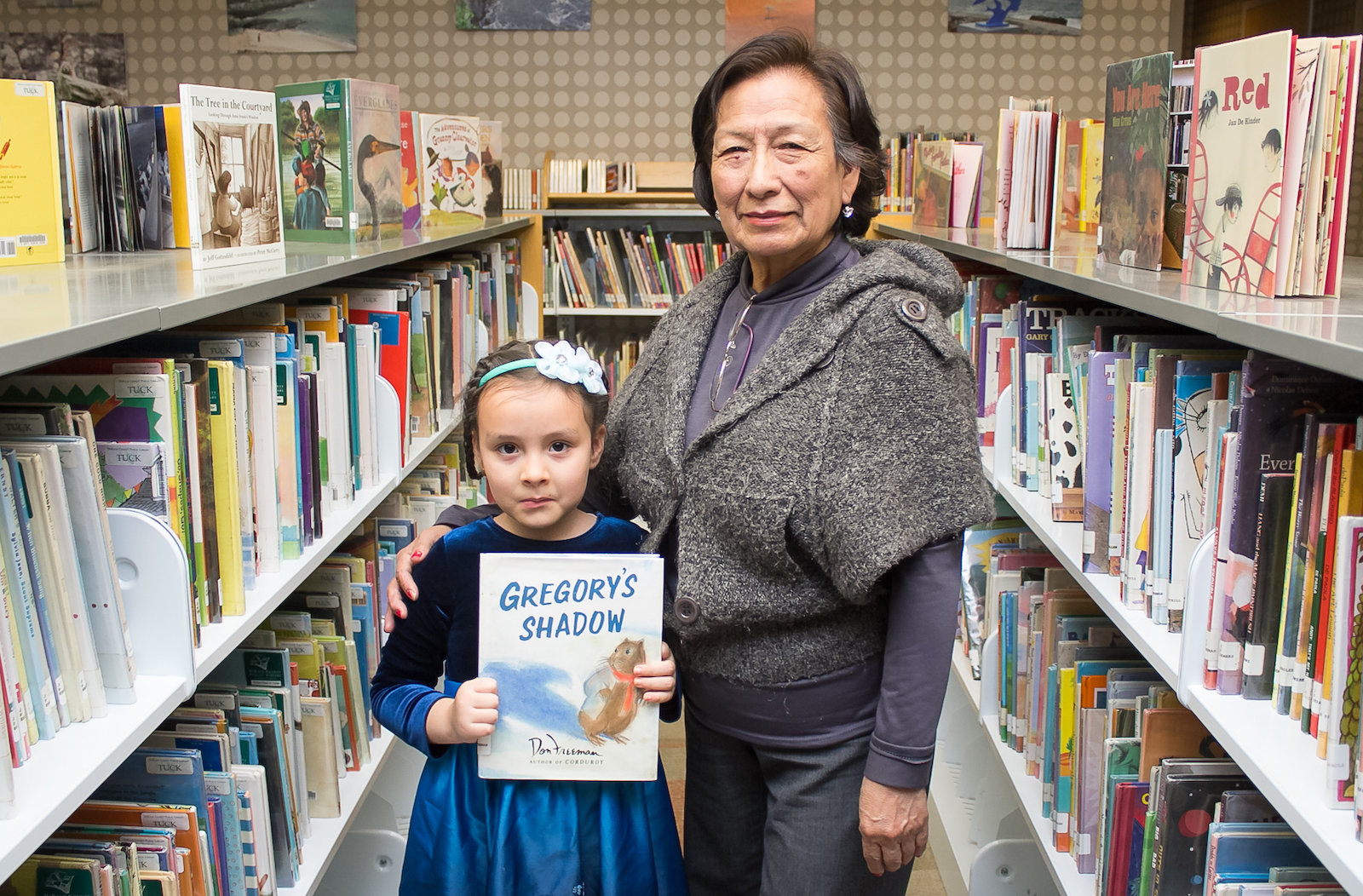 girl holding book standing with grandmother