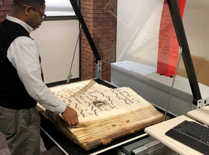 photo of a man scanning pages in a historical book