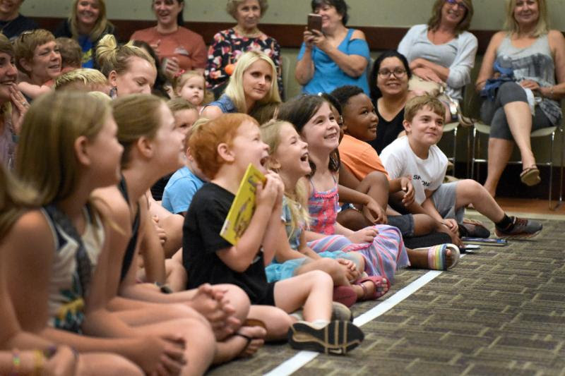 photo of children sitting on the floor laughing during a library event