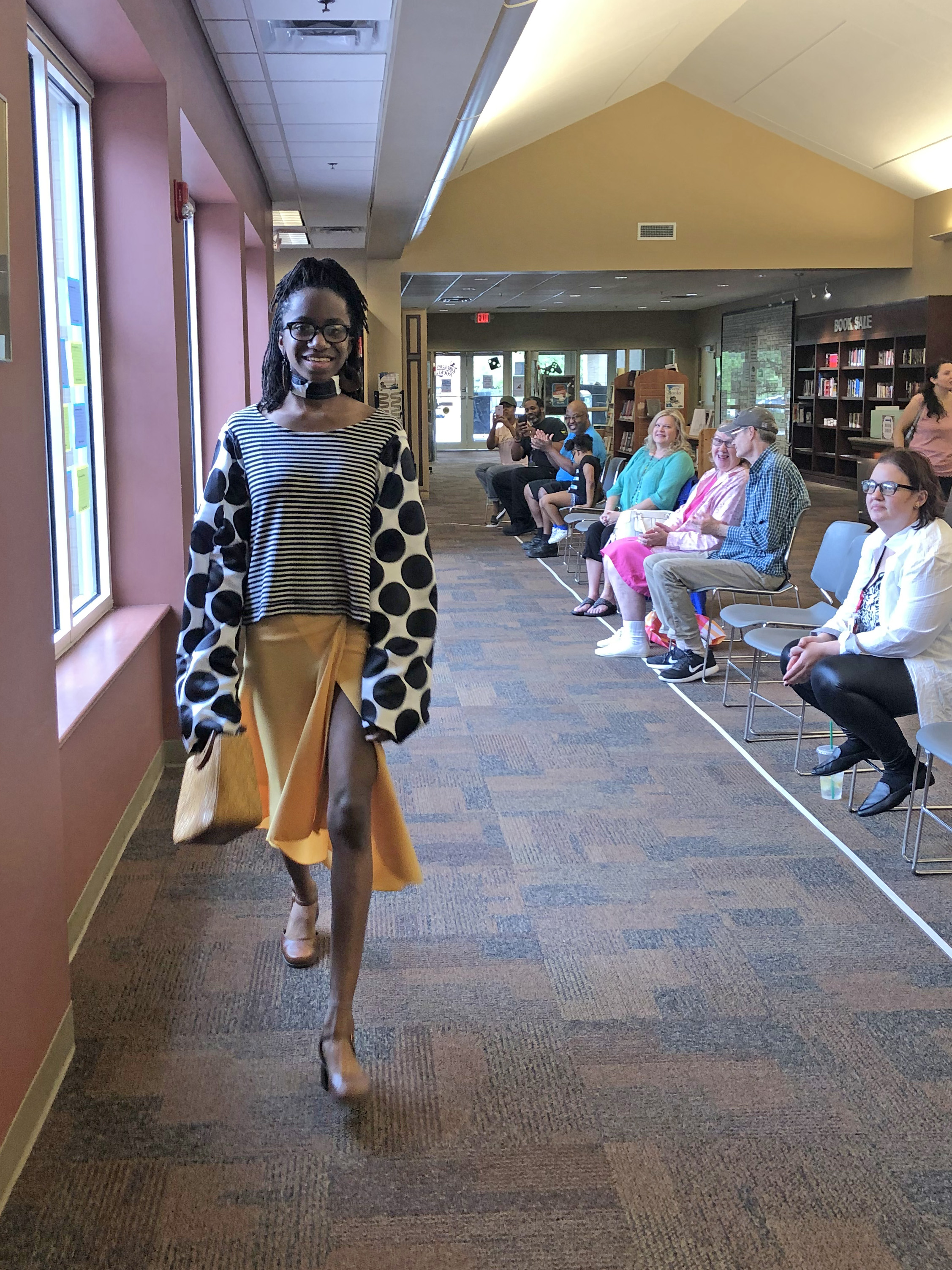 A young lady models clothes created using a sewing machine borrowed from her local library.