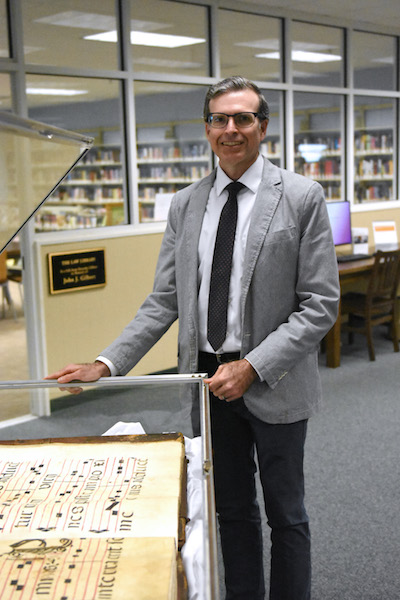 Ben Bryson, assistant director at Marshes of Glynn Libraries, stands next to the codex on  display at Brunswick Library