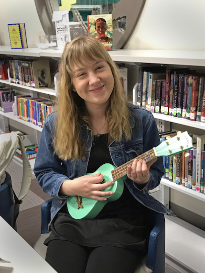 a lady is posing with ukulele