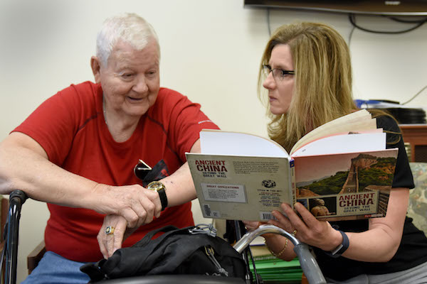 librarian reading book with older man during a community outreach program