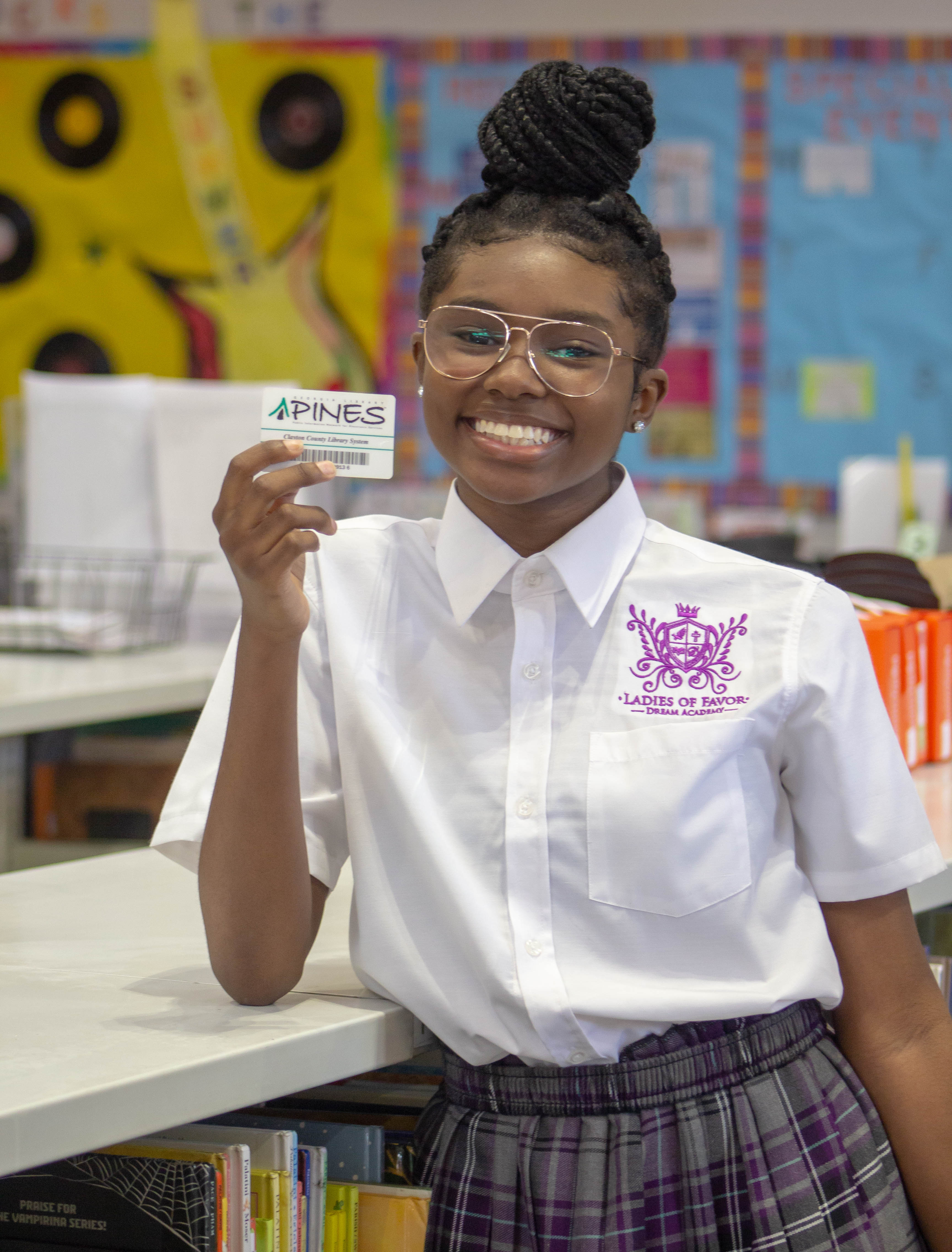 student holding a PINES library card