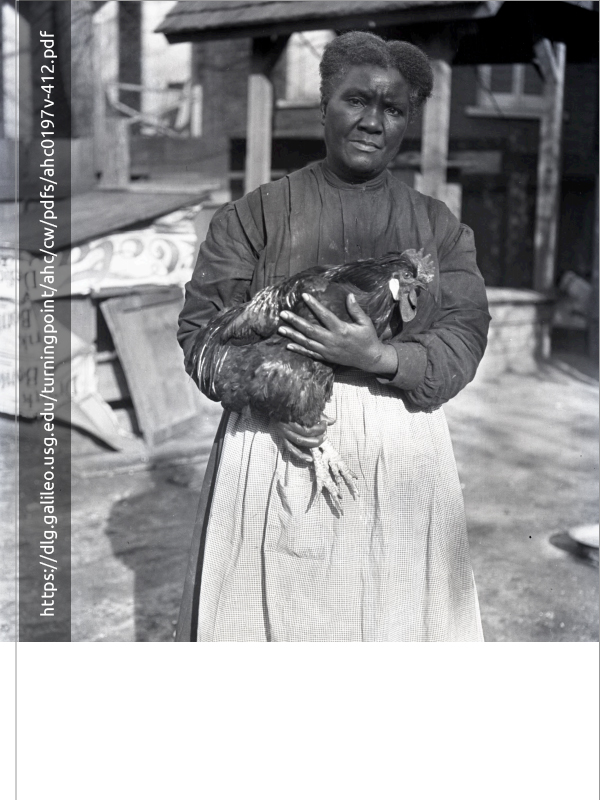 black and white image of an african american woman holding a rooster