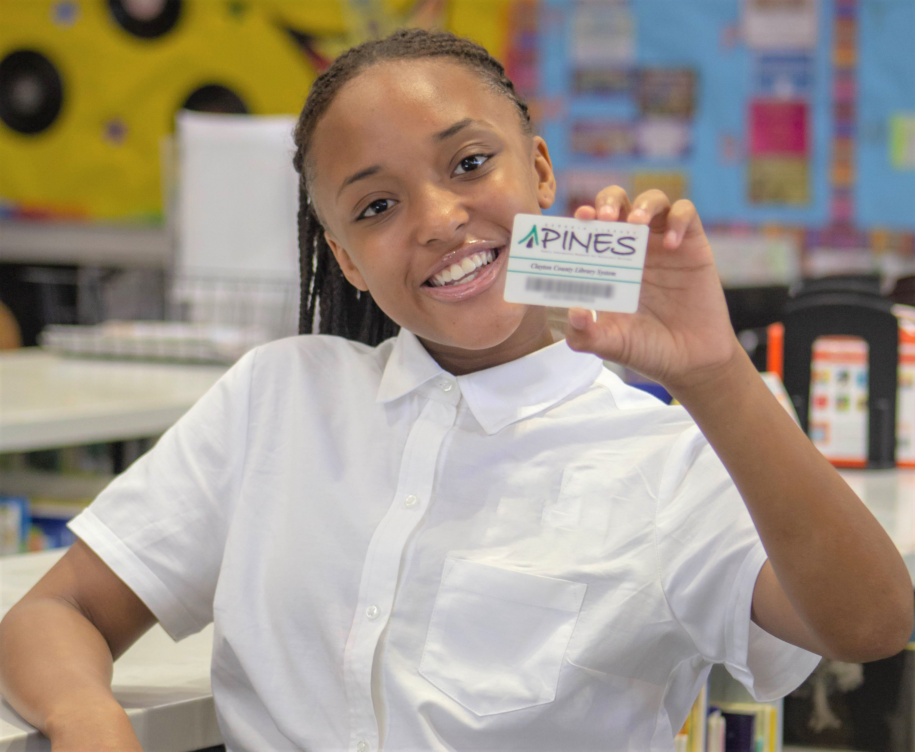 female student smiling and holding a PINES library card