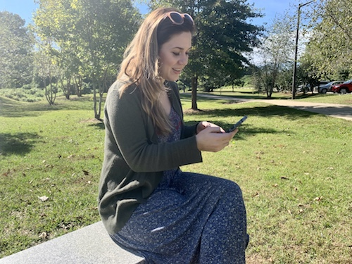 lady using mobile device in public park