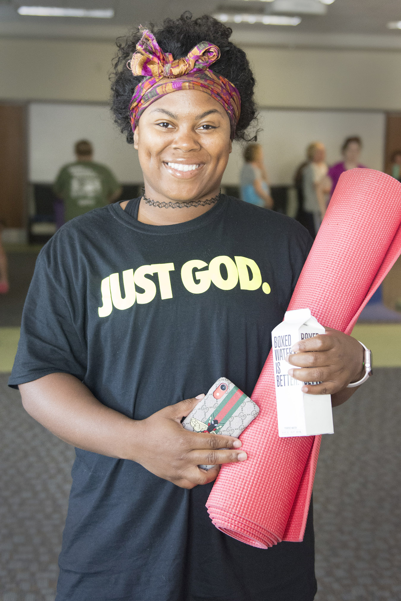 woman smiling while holding a yoga mat