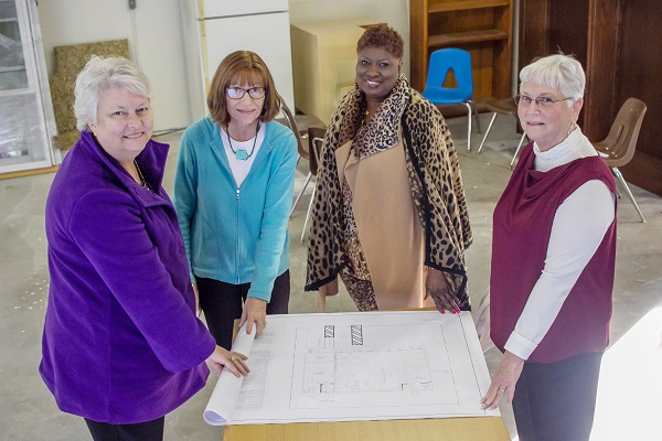 ladies showing off blueprint of new library