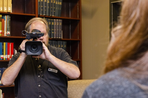 Man using video camera to record woman