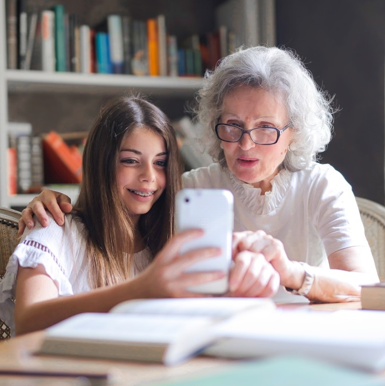 child and grandparent with smartphone