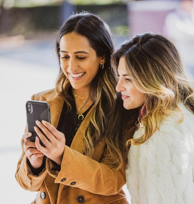 women holding smartphones