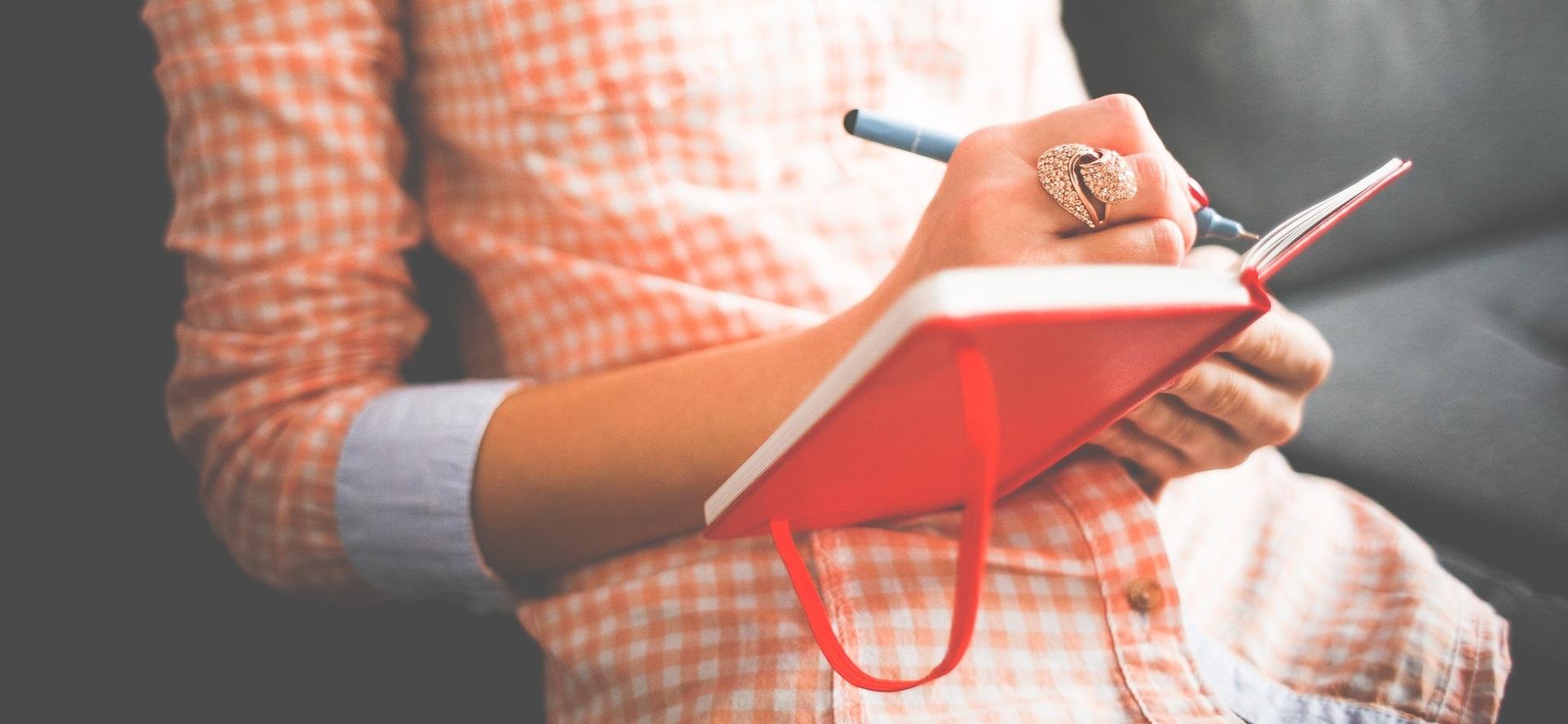 female writing in a journal
