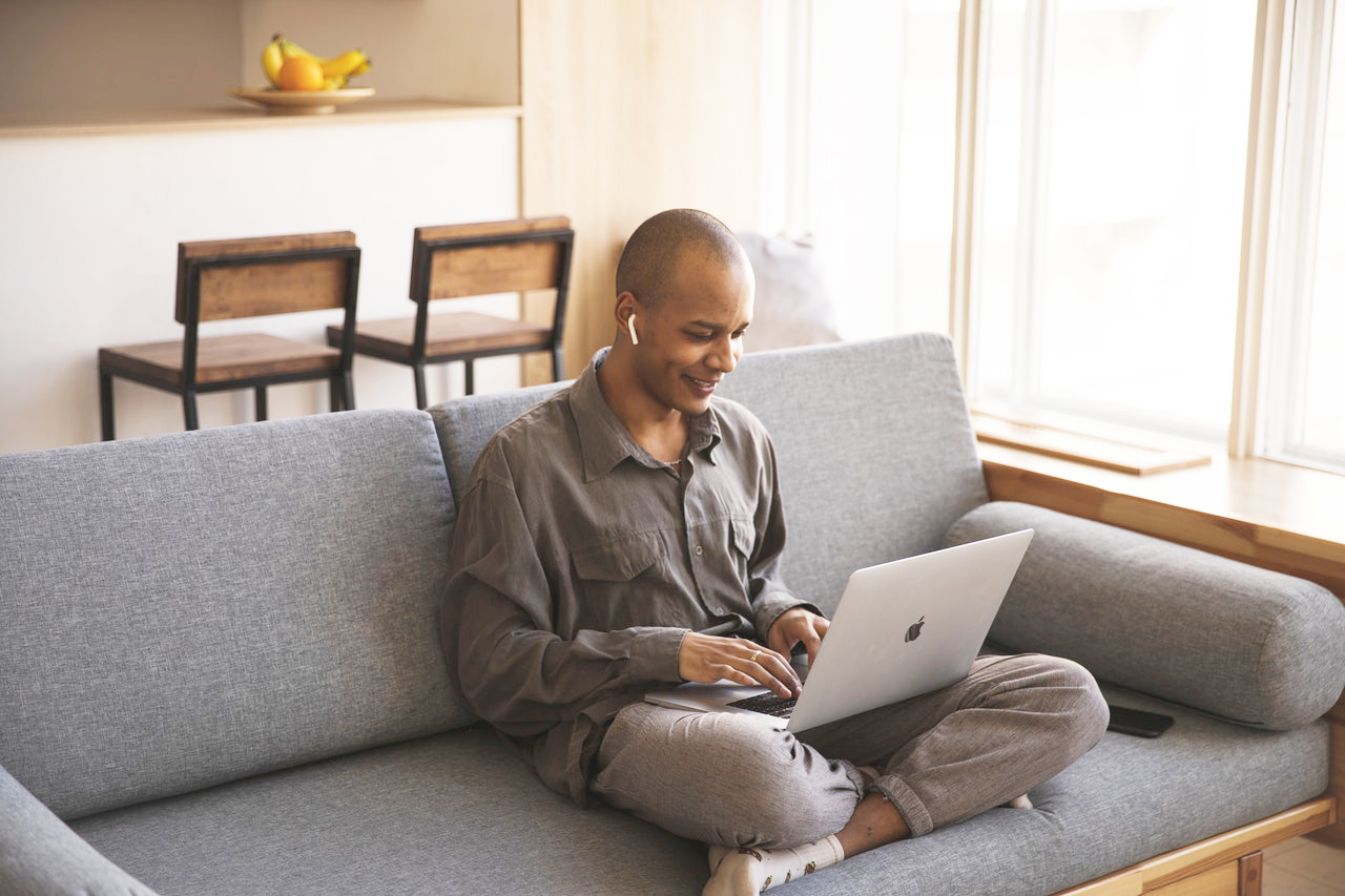 man sitting on couch using laptop