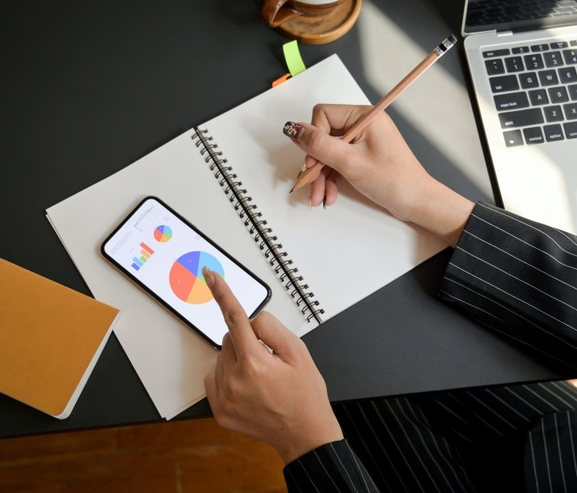 photo of female hands writing in notepad and holding smartphone