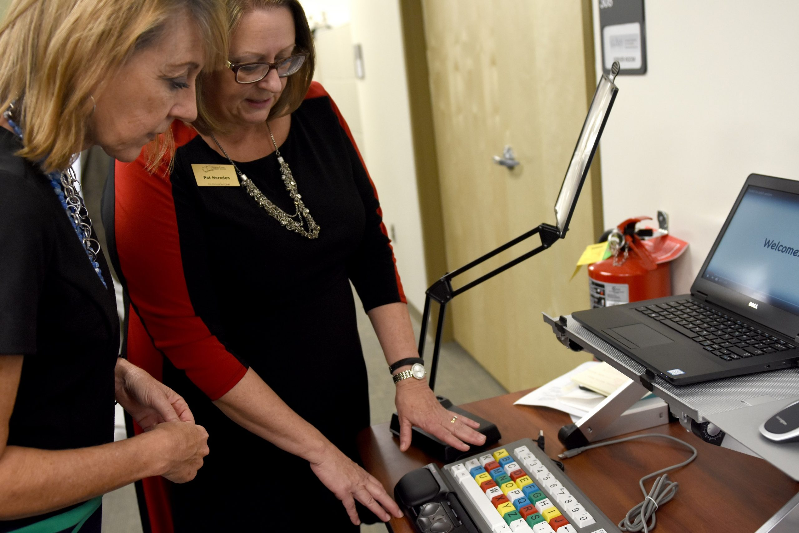 two women looking at library tech for blind and print disabled patrons