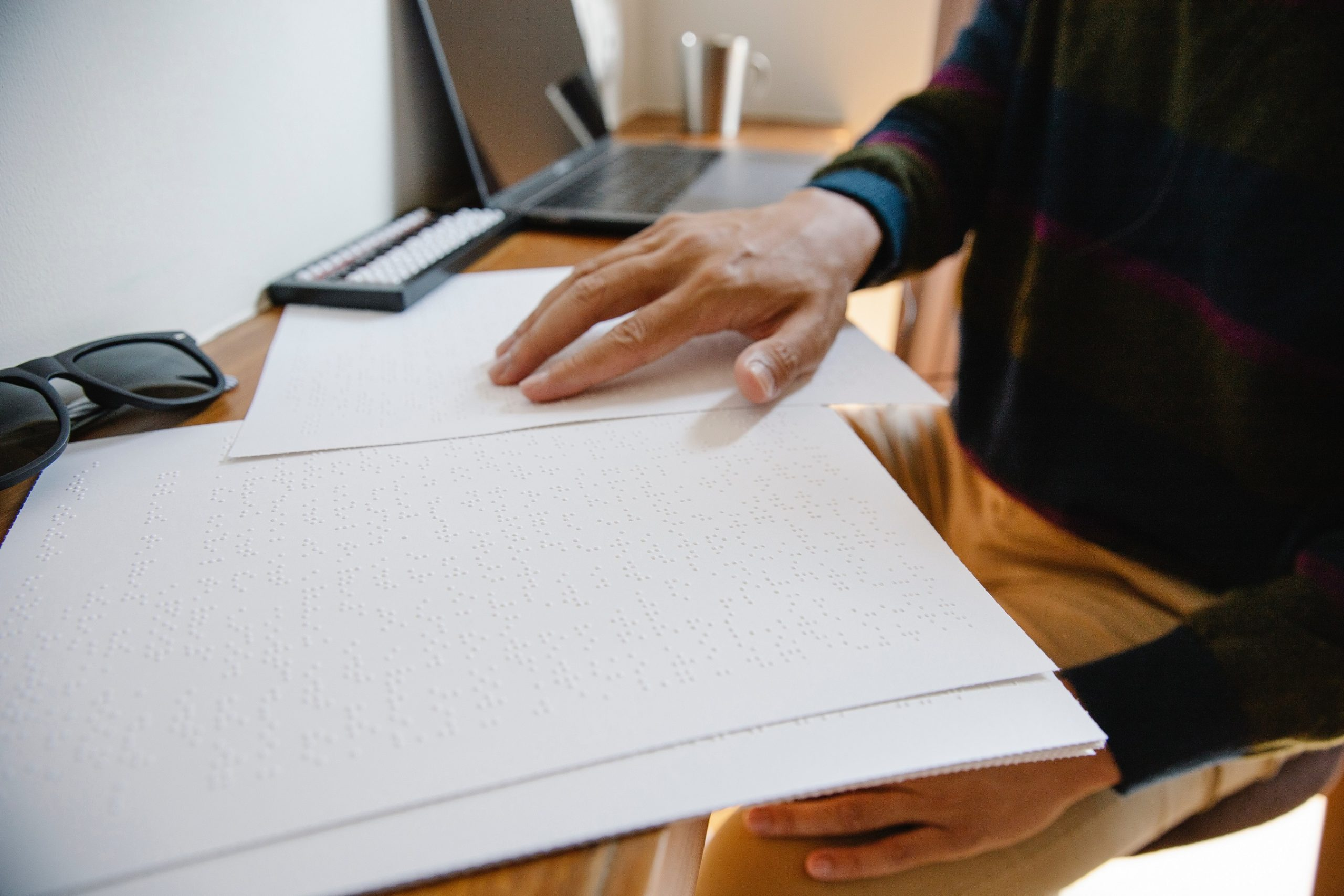 male hand reading braille page