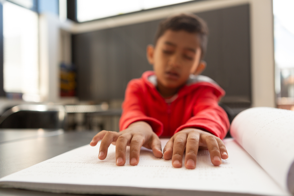 young boy reading braille book